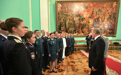 Vladimir Putin with military academy graduates at a reception in their honor.