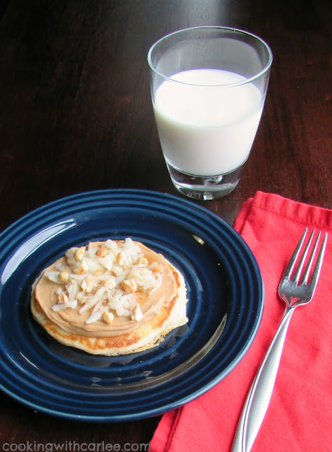 Pancake covered with maple peanut butter, shredded apples and peanuts like a small breakfast pizza with glass of milk