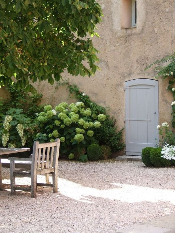 Magnificent #Frenchfarmhouse facade and courtyard with blooming hydrangea, rustic dining furniture, and arched door