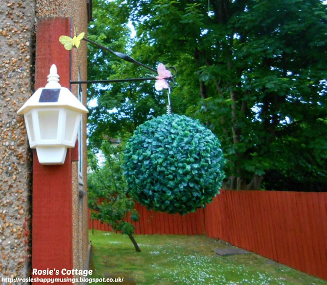 The already present tall post near the front door has been used to add a garden bracket, to this bracket we've added two pretty glittery butterflies (might encourage the real thing?) a large topiary ball for decoration and a useful solar powered lantern.