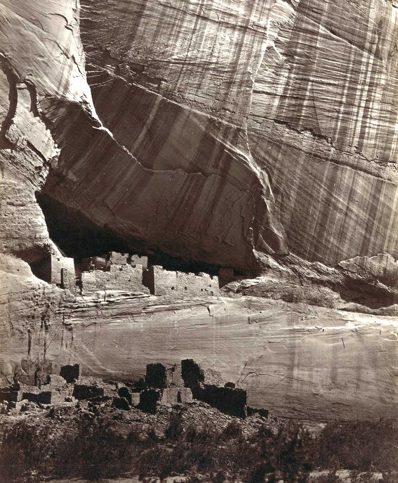 View of the White House, Ancestral Pueblo Native American (Anasazi) ruins in Canyon de Chelly, Arizona, in 1873. The cliff dwellings were built by the Anasazi more than 500 years earlier. At bottom, men stand and pose on cliff dwellings in a niche and on ruins on the canyon floor. Climbing ropes connect the groups of men.