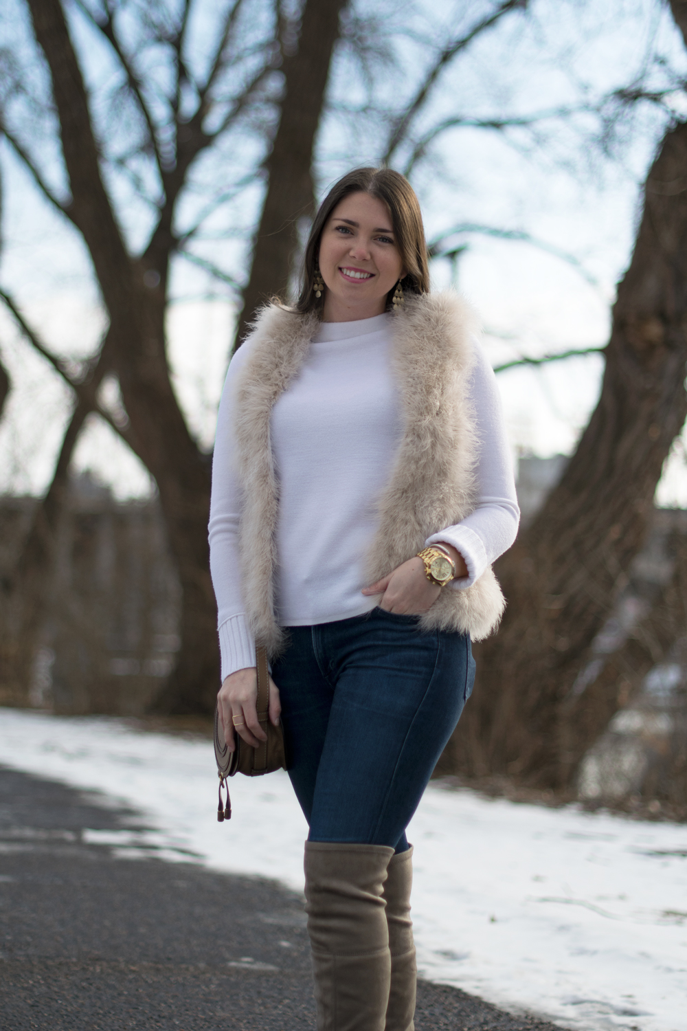 White feather vest with chic outfit.