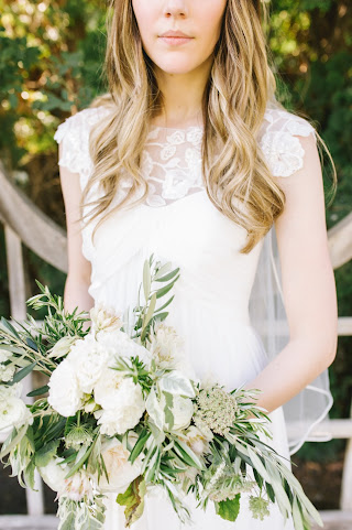 classic bride in a lace dress with a white garden rose and olive bouquet for her classical garden wedding