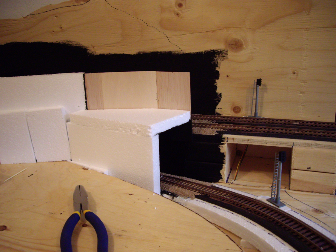 Expanded foam and basswood panels being installed beside ballasted train track to form tunnel walls