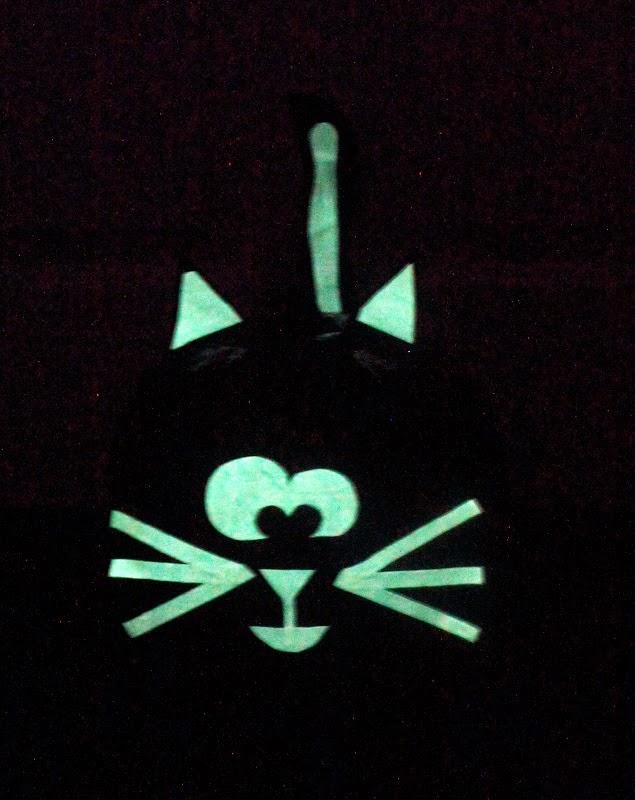 black cat jack o lantern glowing in dark