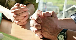 hands clasped in prayer
