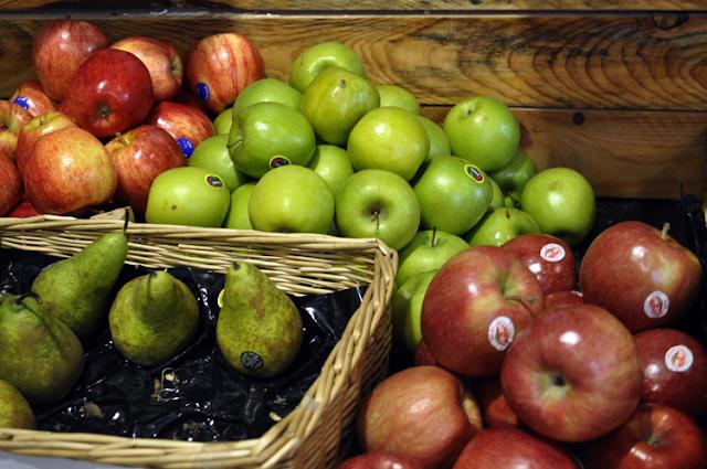 diferentes frutas expuestas, en primer plano peras y manzanas
