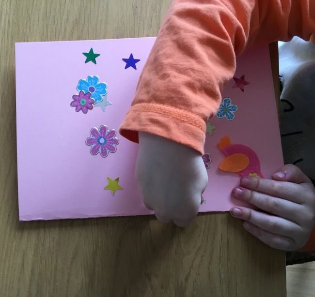 A toddler placing stickers on a pink card