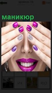 Девушка приложила ладони к лицу с маникюром на ногтях розового цвета