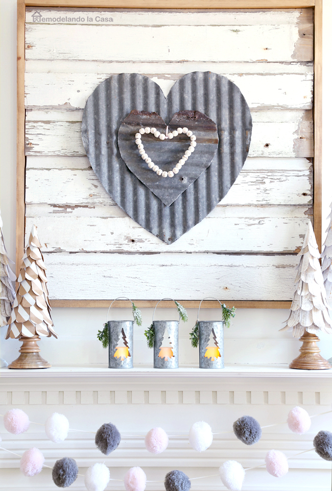 metal hearts wall art and paper trees on white mantel for Valentine's day.