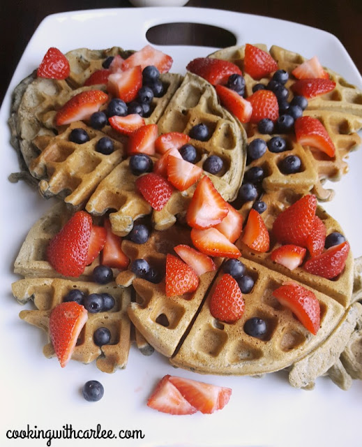 close up of blueberry sourdough waffles with fresh berries on top