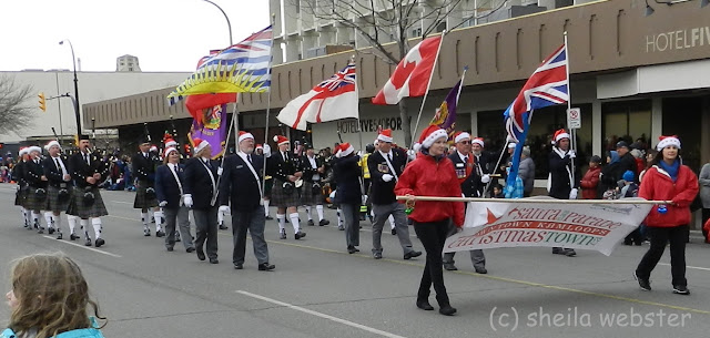 The Pipe Band plays in the parade being led by those carrying flags.