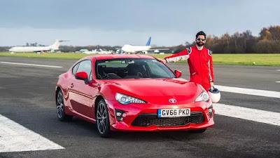 "Dr. Amitas Patelis prie raudono automobilio ""Toyota GT86"""