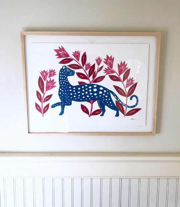 framed tissue paper cut scene of blue leopard surrounded by pink flowers with red leaves hanging on wall