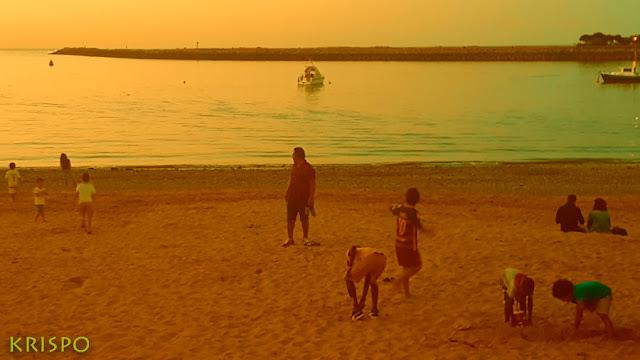 niños jugando en la playa de hondarribia al anochecer