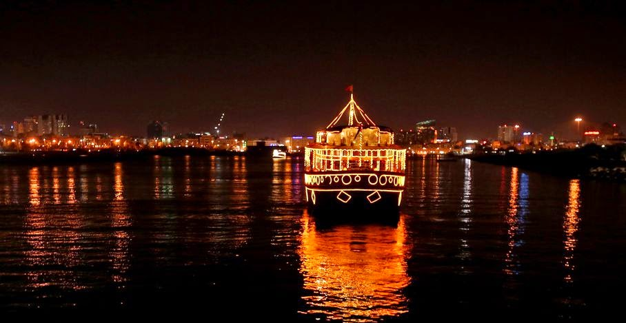 In this Friday, April 25, 2014 photo, a lit boat on the creek waters in Dubai, United Arab Emirates. Unlike the rest of the city, the Dubai Creek area has until now been left relatively untouched by developers, offering a glimpse into the modest beginnings of a city that is now a byword for wealth, excess and overnight development.