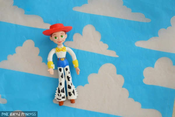 small Jessie cowgirl figure lying on blue sky printed tissue paper