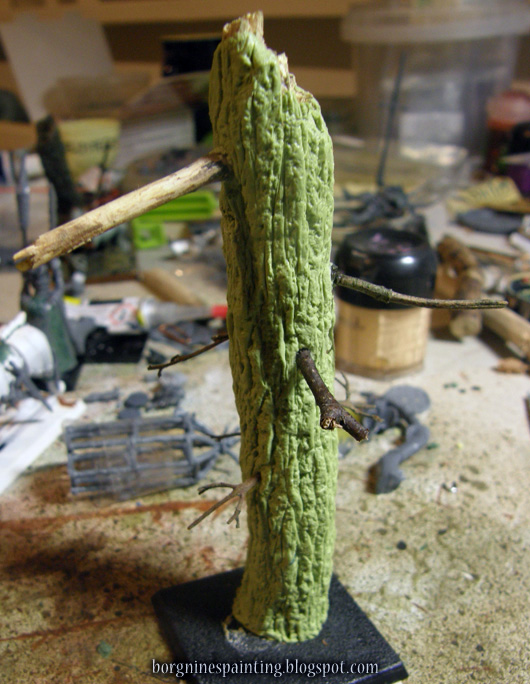 The sculpted tree with bark now has several, unpainted, much smaller twigs stuck inside it - some of them thicker, some thinner and branching.