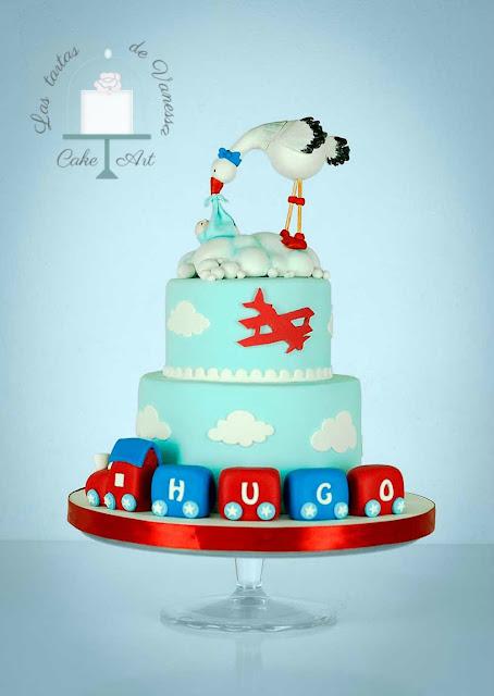 tarta de fondant bautizo cigüeña, tren y avión azul, rojo y blanco