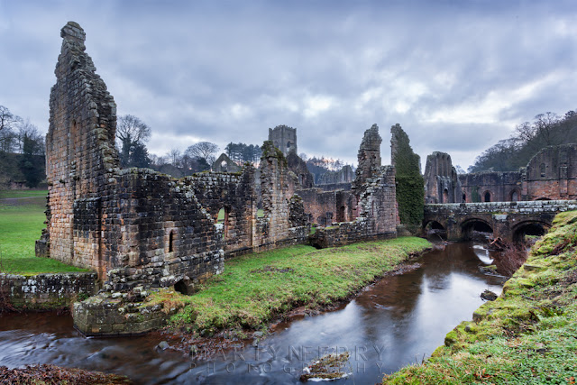 National Trust Cistercian ruins at Fountains Abbey under cloud