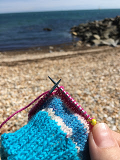 Beach scene with a striped knitted sock in the foreground