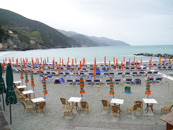 Closed umbrellas on the beach on a cloudy day in Monterosso al Mare, Cinque Terre, Italy