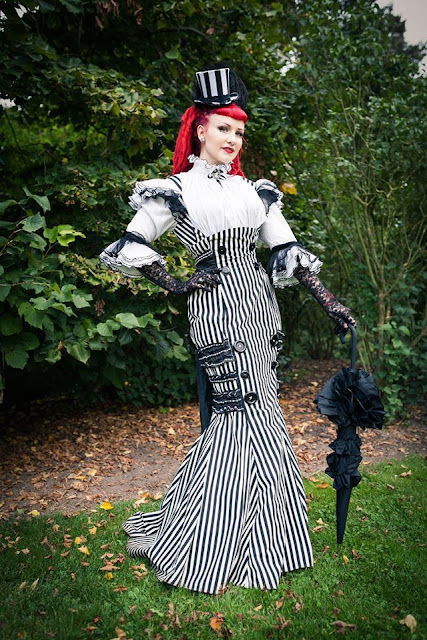 Woman dressed in gothic steampunk clothing. Black and white striped fishtail/mermaid skirt dress with a top hat and parasol