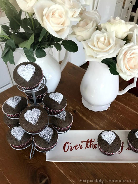 Best Valentine Cupcakes in a metal stand on a table with flowers and a holiday dish