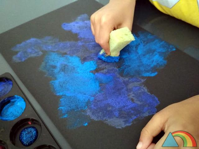 Pintura de tonos azules aplicada sobre cartulina negra con esponja