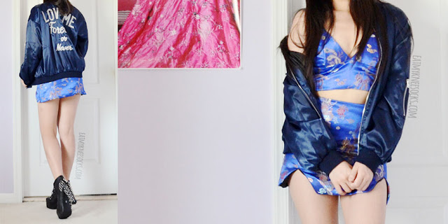 "Royal navy blue silky satin bomber jacket with ""love me forever or never"" typographic embroidery, worn with blue Chunli oriental silk bralet and skirt from O-Mighty."