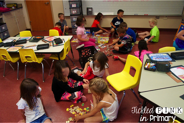 students spread around the classroom putting puzzles together
