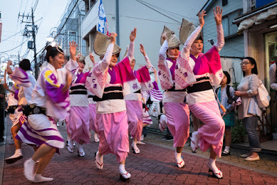Women dance at the 60th Koenji Awa-Odori along a narrow alley.
