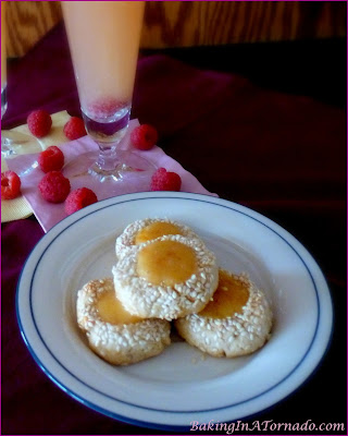 Orange Sesame Thumbprint Cookies, sesame studded cookies filled with an orange jam and powdered sugar center. A fun alternative to the original cookie flavors. | Recipe developed by www.BakingInATornado.com | #recipe #cookies