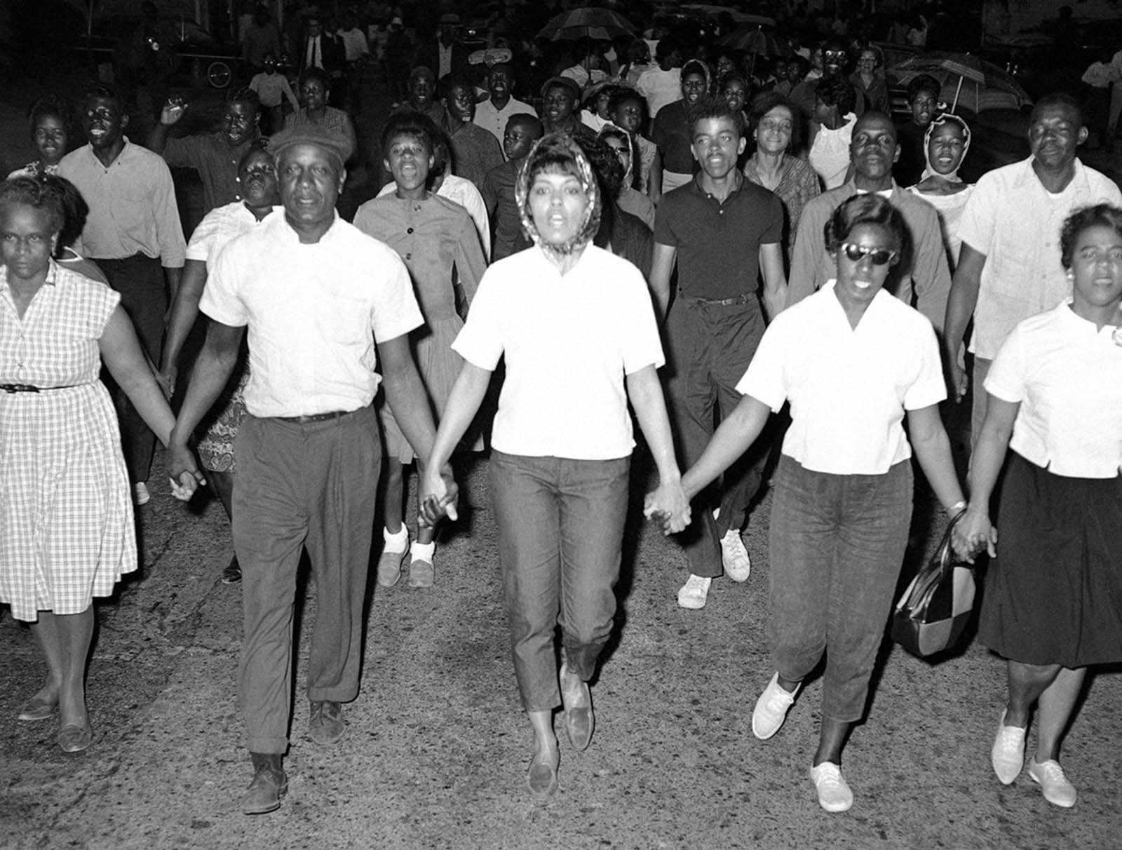 Civil rights marchers walk through the streets of downtown Cambridge, Maryland, on May 12, 1964. The National Guard were deployed to keep order after a violent confrontation the night before.