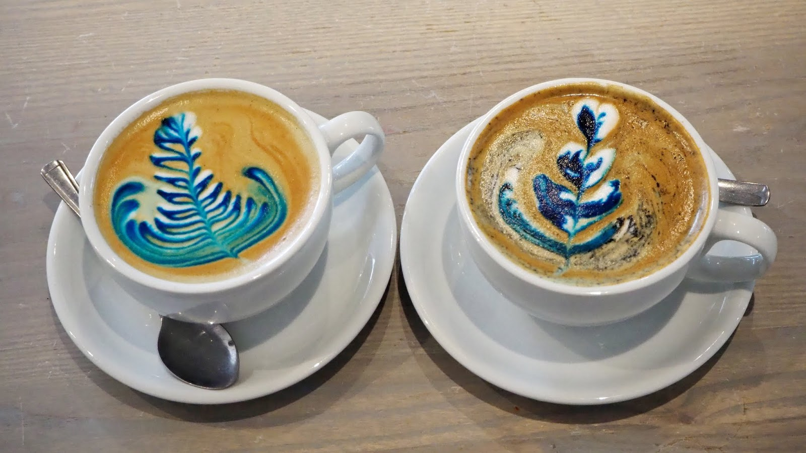 Two rainbow lattes with blue latte art