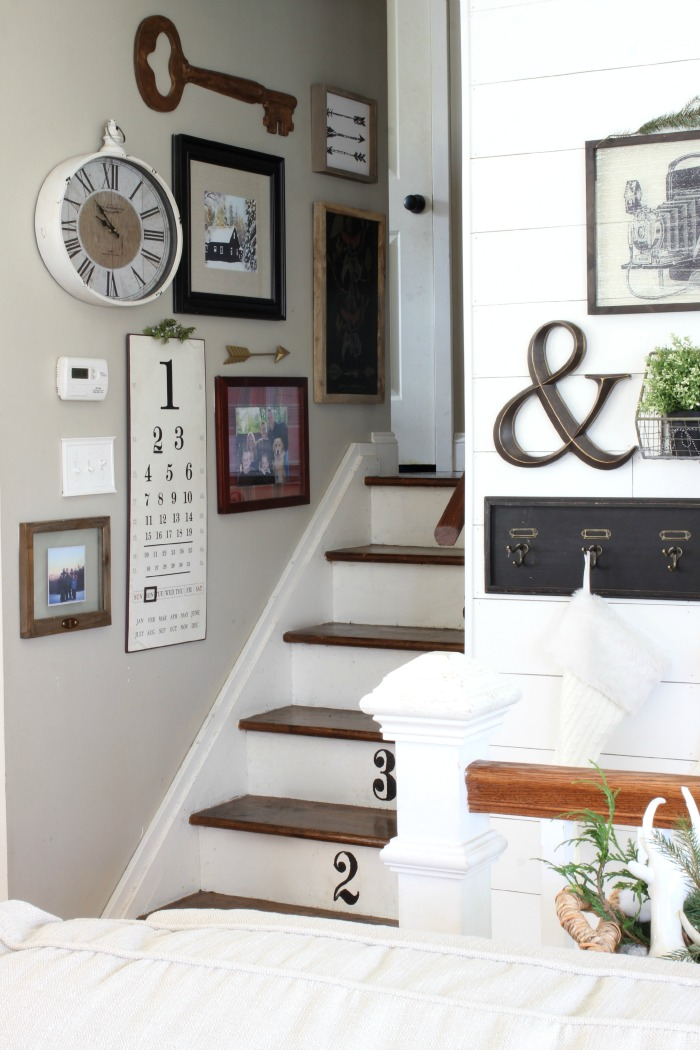 Gallery wall up the stairs with black and white accents and plank wall - www.goldenboysandme.com