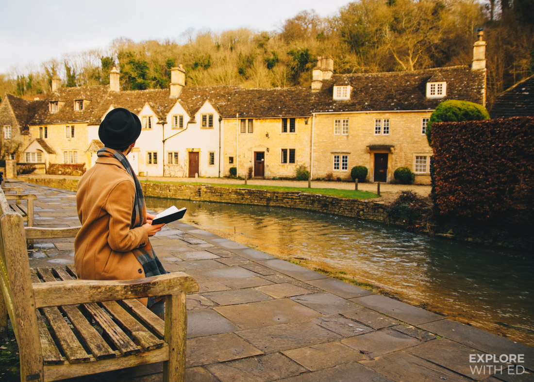 Reading a book by the river in Castle Combe, England's Prettiest Village