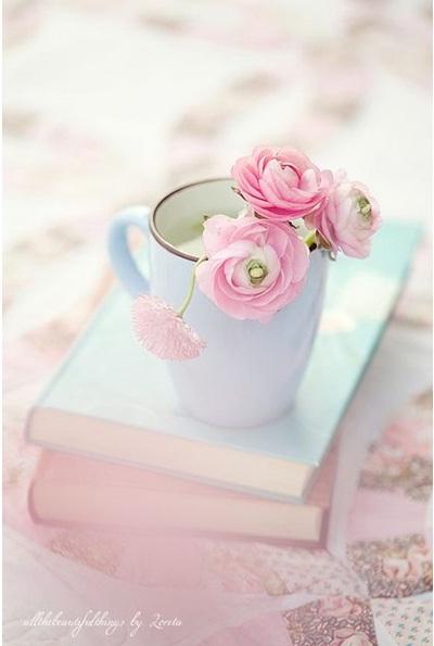 Gabungan antara mug, bunga potong, dan buku-buku menjadi hiasan meja yang cantik.