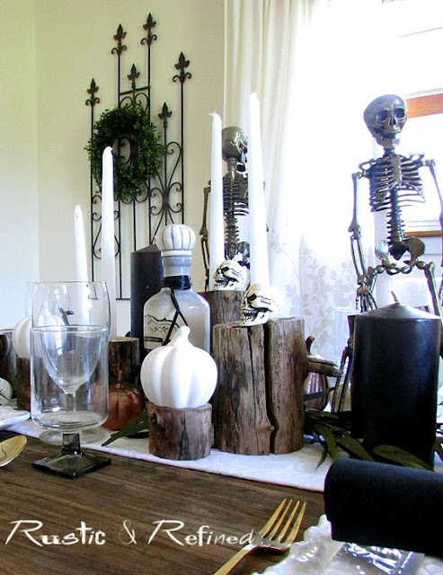 Halloween spooky tablescape with skeletons centerpiece and wooden logs