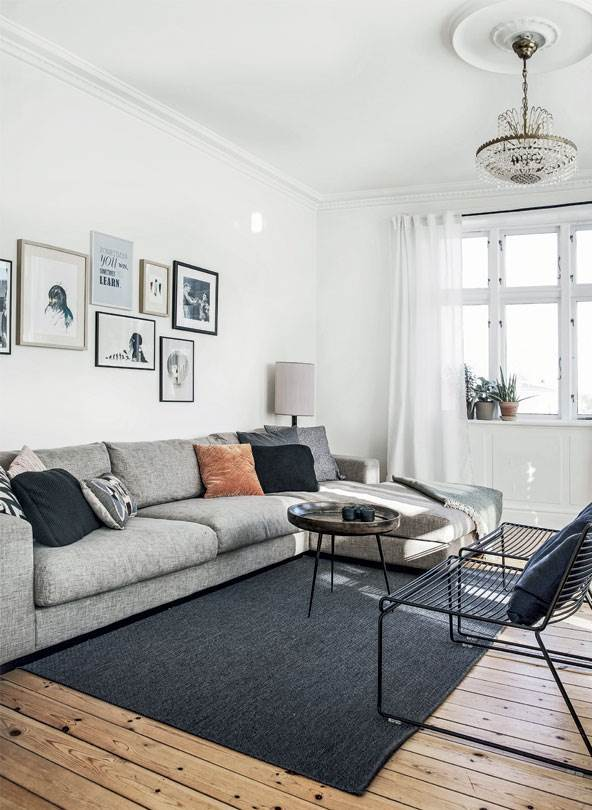 scandinavian apartment with wooden floors, mid century modern furniture , gray sofa, gallery wall, dark carpet