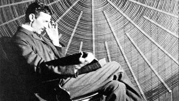 Una imagen de Nikola Tesla sentado y leyendo delante de una bobina espiral de su transformador de alta tensión.