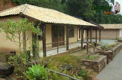 Construção de cabana rústica com a base de pedra, os pilares de madeira no terraço e o piso de cimento queimado branco com a cobertura com telha colonial.