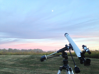 telescope in field at sunset