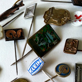 Selection of vintage enamelled tie pins in various shapes and colours.