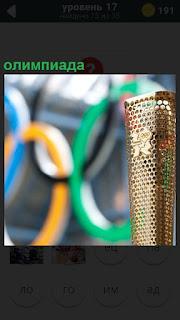 Позолоченный кубок с олимпиады представлен на фоне разноцветных колец