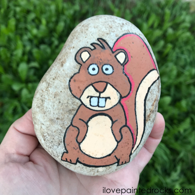 squirrel painted rock in the garden