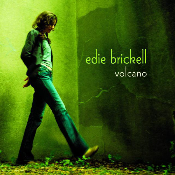 Cover to Edie Brickell album 'Volcano' showing her at the corner of two green walls kicking at some leaves on the ground