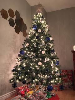 Arvore de natal com decoracao azul, prata e branca e presentes