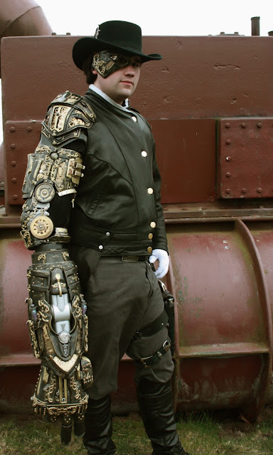 Man wearing steampunk clothing and a big mechanical steampunk arm gadget