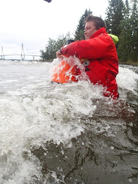 Pelastautumispukuinen henkilö taistelee aaltoa vastaan vesikiikarin kanssa meressä